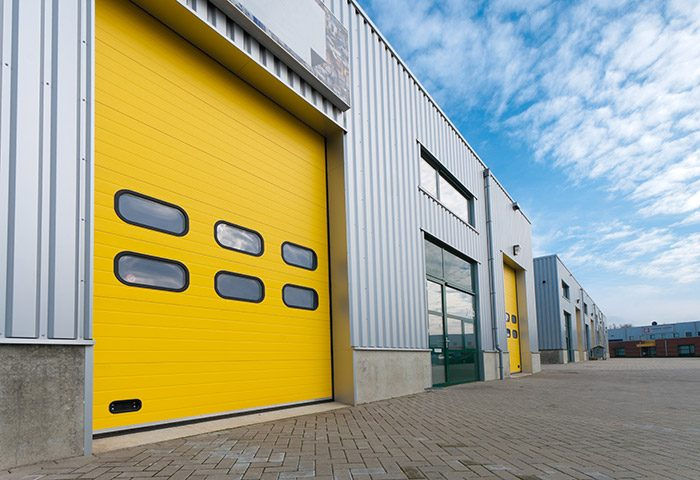 Industrial property warehouse with green and yellow roller doors.