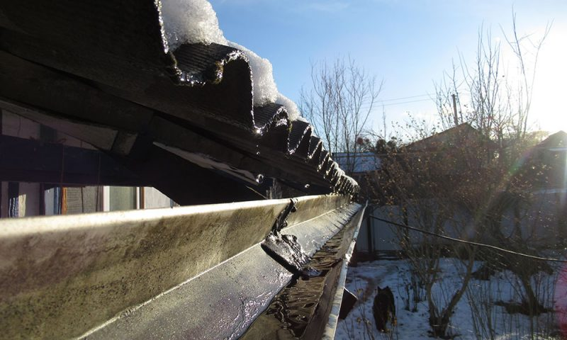 Melting snow running into guttering in the aftermath of bad weather, blue skies